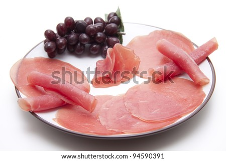 Salmon ham with grapes on plate - stock photo