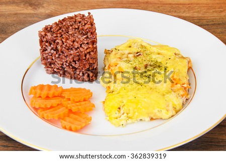 Salmon in cream with onions and carrots, red rice side dish Studio Photo