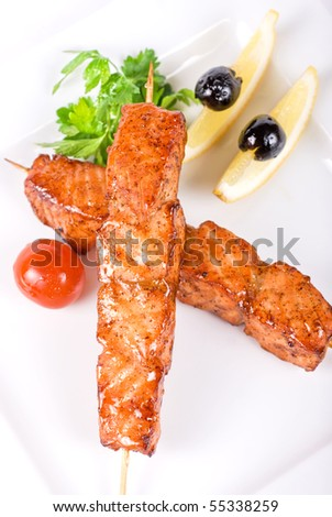 salmon kebab at plate with green lettuce and lemon on a white - stock photo