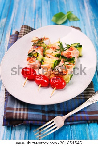 salmon kebab: skewers with salmon, cherry tomatoes and zucchini on  rustic wooden blue planks - stock photo