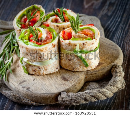 Salmon lavash rolls with fresh salad leafs - stock photo