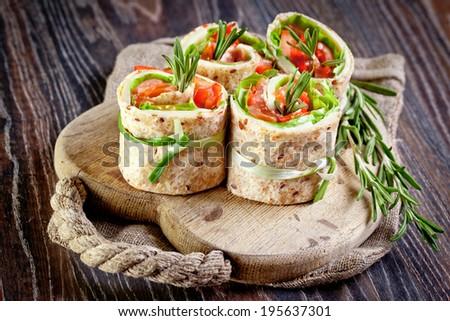 Salmon lavash rolls with fresh salad leafs - stock photo