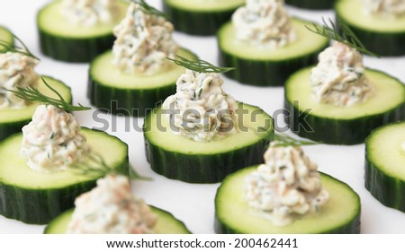 Salmon mousse served on cucumber slices, garnished with dill. - stock photo