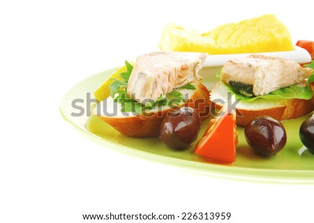 salmon on baguette slices with butter and dark olives