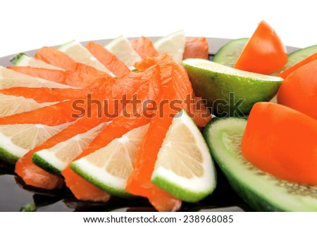 salmon on plate with tomatoes and lemon on black - stock photo
