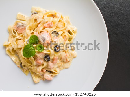Salmon pasta shot with creamy sauce and olives on white plate. See more italian and healthy - stock photo