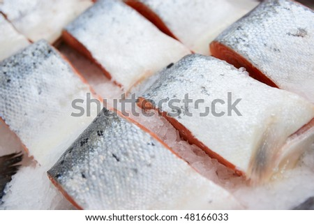 Salmon pieces on cooled market display, closeup - stock photo