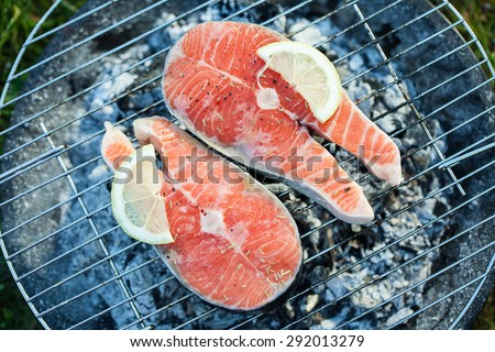 Salmon preparation process on wooden grill. Grilled fish steaks on fire. Top view - stock photo