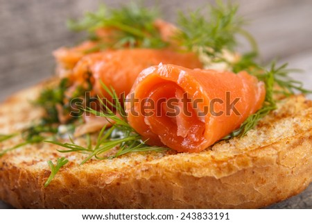 Salmon rolls with dill on toasted bread , shallow dof - stock photo