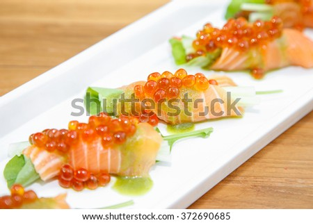 salmon rolls with vegetable and red caviar.