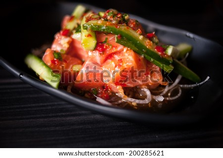 Salmon salad on black plate and black background. Selective focus, shallow depth - stock photo