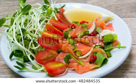 Salmon salad on wood background