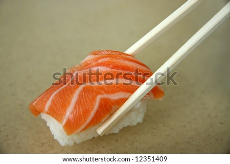 Salmon sashimi held in chopsticks traditional japanese cuisine