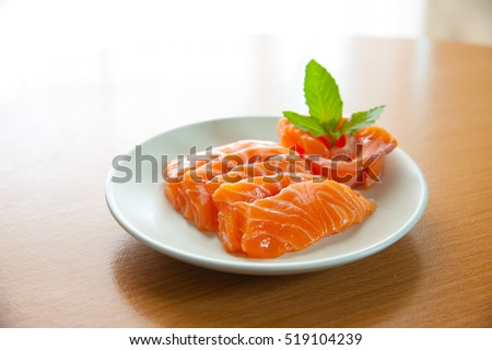 Salmon sashimi on wooden table in center