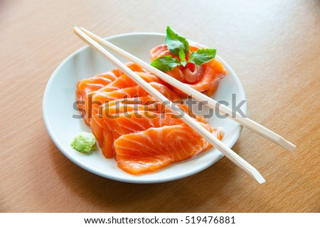 Salmon sashimi on wooden table with chopsticks in center