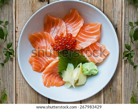 Salmon sashimi sushi put into white bowl with wood background - stock photo