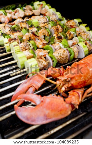 Salmon Skewers and Lobster are on the barbecue. - stock photo
