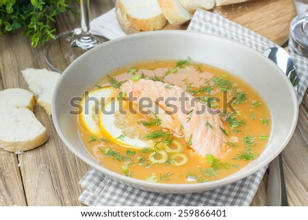 Salmon soup sprinkled with dill, served with green olives and lemons on wooden desk background - stock photo