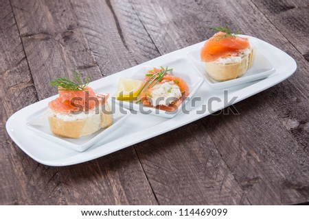 Salmon starters on small plates against wooden background