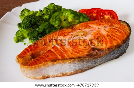 Salmon steak fillet with broccoli on plate