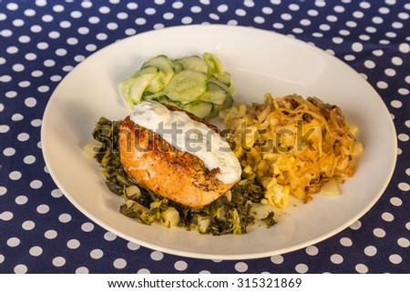 Salmon Steak on turnip greens with chopped turnips.  Served with German Spatzle and Cucumber Salad and topped with dill and sour cream. Round white plate on unique blue and white polka dot tablecloth. - stock photo
