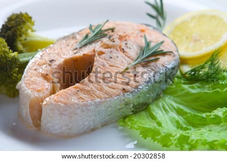 Salmon steak prepared on steam on white plate - stock photo