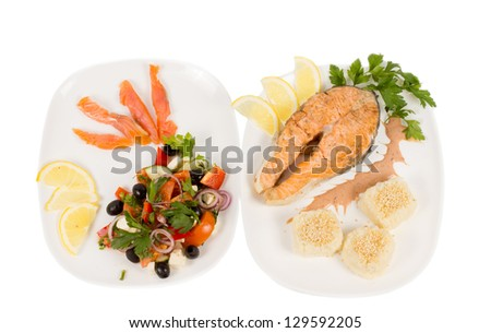 Salmon steak served with accompaniments of sliced smoked salmon and fresh mixed salad on two plates