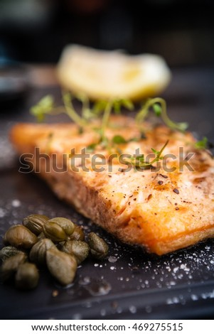 Salmon steak served with pomegranate sauce on a warm plate