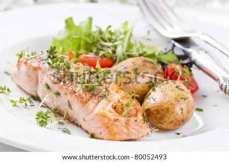 salmon steak with potato and salad - stock photo
