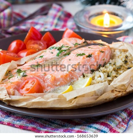 Salmon steak with rice, herbs, tomatoes, baked in parchment paper, tasty dinner - stock photo