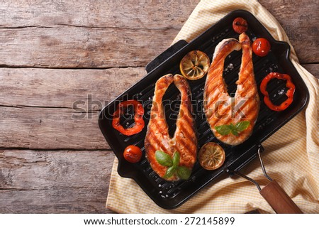Salmon steak with vegetables on a grill pan. horizontal view from above  - stock photo