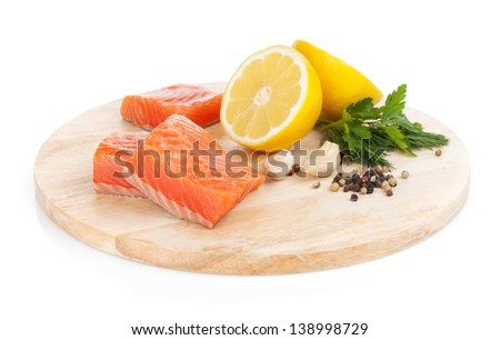 Salmon steaks on cutting board with lemons and herbs. Isolated on white background - stock photo
