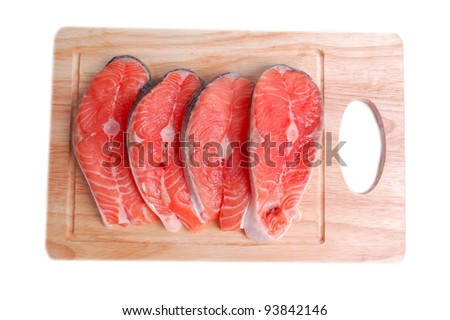 Salmon steaks on wooden board - stock photo