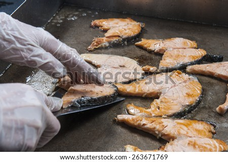 Salmon steaks with chefs hands cooking on grill hot plate at a hotel restaurant buffet - stock photo
