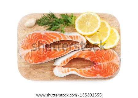Salmon steaks with herbs and lemon slices on cutting board. Isolated on white background - stock photo