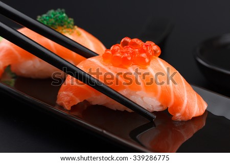 Salmon sushi nigiri in chopsticks over black background - stock photo