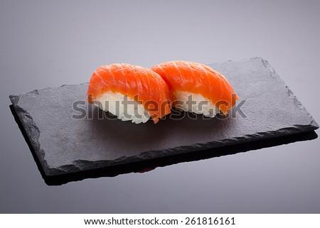 Salmon sushi nigiri on a stone plate over black backround - stock photo