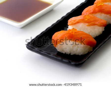 Salmon Sushi on the black plate with soy souse on a white table.