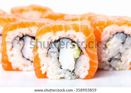 Salmon sushi roll with snow crab and cucumber. Macro. Photo can be used as a whole background. - stock photo