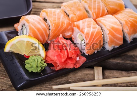 Salmon sushi rolls on a wooden background - stock photo