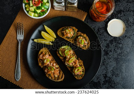 Salmon tartar on crispy toast with crisp cucumber salad and chilli pepper - stock photo