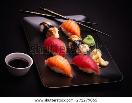 Salmon, tuna and eel sushi with chopsticks, dark background - stock photo
