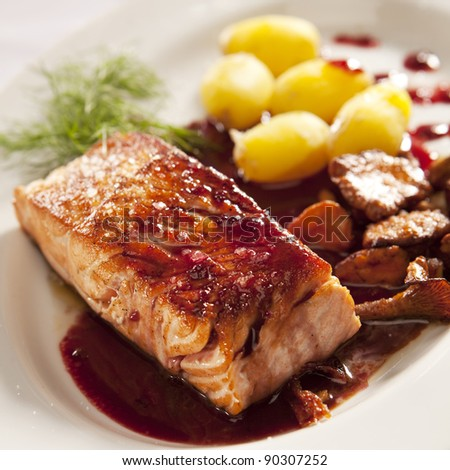 Salmon with black currant sauce, mushrooms and potatoes - stock photo