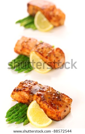 Salmon with honey mustard marinade and asparagus on white background.