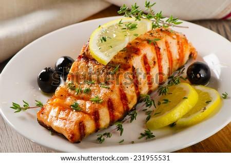 Salmon with lemon, olives and  herbs. Selective focus - stock photo