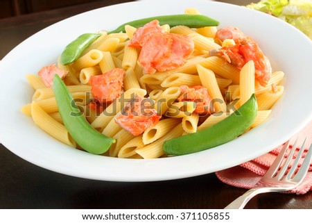 Salmon with penne and sugar snap peas is a healthy way to eat your way to a slimmer you for Spring - stock photo
