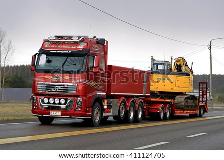 SALO, FINLAND - APRIL 22, 2016: Red Volvo FH16 750 transports New Holland crawler excavator on low bed trailer along highway on rainy evening in South of Finland. - stock photo