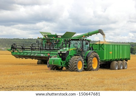 SALO, FINLAND - AUGUST 10: John Deere combine harvester s670i unloads grain on trailer at the annual Puontin Peltopaivat Agricultural Harvesting and Ploughing Show on August 10, 2013 in Salo, Finland. - stock photo