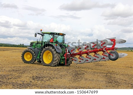 SALO, FINLAND - AUGUST 10: John Deere 6210R Agricultural Tractor and Agrolux plow at the annual Puontin Peltopaivat Agricultural Harvesting and Ploughing Show on August 10, 2013 in Salo, Finland. - stock photo