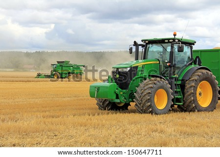 SALO, FINLAND - AUGUST 10: John Deere 7280R Tractor and Combine Harvester T560 at the annual Puontin Peltopaivat Agricultural Harvesting and Ploughing Show on August 10, 2013 in Salo, Finland. - stock photo